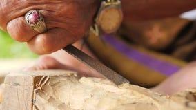 Woodcarver robi cyzelowaniu z ostrzy narzędziami na drewnianym workpiece Tradycyjny balijczyka posążka robić proces 4 K bali Indo zbiory