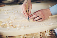 Woodcarver tool cuts the wood on table Stock Photography