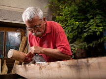 Woodcarver working with mallet and chisel 6. Old woodcarver working with mallet and chisel 6 Royalty Free Stock Photos