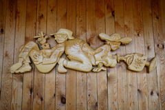 Woodcarving – the song `the Gardeners`. Panels, carved on a pine Board mounted on the wall of a country house, has a playful theme: while the wife works Stock Photography