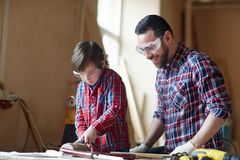 Woodcarving with father Stock Photography