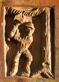 Woodcarving of man chopping tree Stock Image