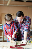 Woodcarving work. Little boy woodcrafting while his father consulting him Stock Photo
