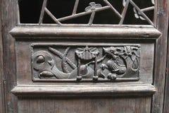 Woodcarvingdekorationen mit einem Drachen an einer alten Bauholztür, Daxu, China Stockfotos