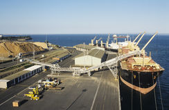 Woodchip being loaded on to bulk carrier ship for export Stock Photos