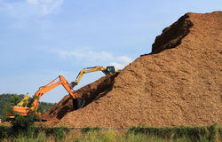 Woodchip Mountain with Backhoes working Stock Photos