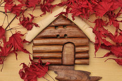 Woodcraft cabin house and dry maple leaves. On wood background stock images