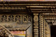 Woodcrafted gudar i dörr för slott` s i Lalitpur Nepal royaltyfri bild