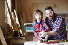 Woodcrafters. Little boy and men with chisel woodcarving together Stock Photography