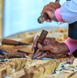 Woodcraftsman is carving wood Stock Photo