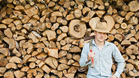 Woodcutter with straw hat on a background of wood Royalty Free Stock Photography