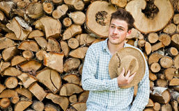 Woodcutter with straw hat on a background of wood Royalty Free Stock Image
