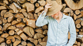 Woodcutter with straw hat on a background of wood Royalty Free Stock Photos