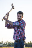 Woodcutter. Lumberman cuts wood with his strong axe Stock Image