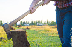 Woodcutter. Lumberman cuts wood with his strong axe Stock Photos