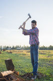 Woodcutter. Lumberman cuts wood with his strong axe Stock Photography