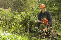 Woodcutter resting from work. With the chainsaw royalty free stock photos