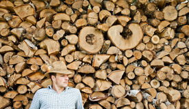 Woodcutter with straw hat on a background of wood Stock Photo