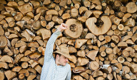 Woodcutter with straw hat on a background of wood Stock Image