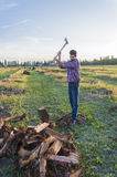 Woodcutter at work. Lumberman cuts wood with his strong axe Royalty Free Stock Photo