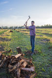 Woodcutter at work. Lumberman cuts wood with his strong axe Royalty Free Stock Photos