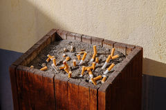 Woodden ashtray with sand full of smoked cigarettes Stock Image