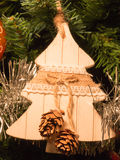 Woodden fir decoration on christmas tree with pine cone Stock Photo