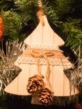 Woodden-Tannendekoration auf Weihnachtsbaum mit Kiefernkegel Stockfoto