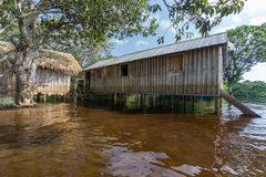Woode houses built on high stilts over water, Amazon rainforest Stock Photo
