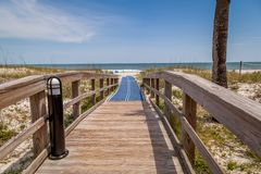 Wooded bridge over the sand dunes on a beautiful blue sky day. royalty free stock photo