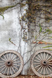 Wooded wagon wheel. Antique and weathered wood cart wheel with vine leaves Royalty Free Stock Photo