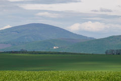 Wooded hill above green agricultural country Stock Photos