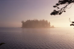 Wooded island in lake. Scenic view of wooded island in picturesque lake at sunset or sunrise Stock Photography