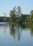 Wooded Island Reflected in Calm Lake Stock Photos