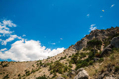 Wooded mountain range. Bottom view of the rocky hill, two paraglider in the sky Stock Photos