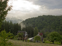 The wooded mountain slopes in the fog under the morning sun thro Royalty Free Stock Images