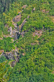 Wooded mountainside with waterfalls. At sunny day stock photography