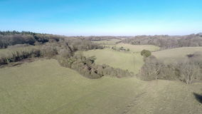 Wooded Valley. Aerial footage moving slowly down a valley with woodland at the edges stock video footage
