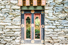 Wooded window and rock wall from bhutan Royalty Free Stock Photos