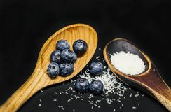 Woodem spoons with shredded coconut and blueberries stock photos