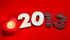 Wooden 2013 year number with a burning candle Stock Photos