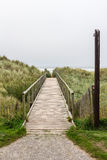 Wooden access pathway to the beach. Wooden pathway crossing the dunes towards the beach. The footpath seems to rise towards the vanishing point in the horizon Royalty Free Stock Image
