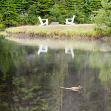 Wooden adirondack chairs by the lake Stock Photo