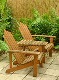 Wooden Adirondack chairs in tropical backyard Royalty Free Stock Images