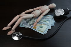 Wooden Adult Human Figurine, Dollar Cash And  Medical Equipment Royalty Free Stock Photos