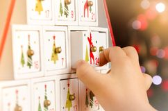 Wooden advent calendar Christmas tree and a child`s hand royalty free stock photo