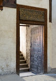 Wooden aged decorated door and beige plaster wall leading to stone staircase royalty free stock photo