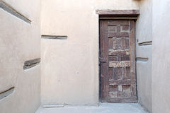 Wooden aged decorated door and stone wall Stock Photography