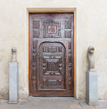 Wooden aged engraved decorated door and stone wall Royalty Free Stock Image