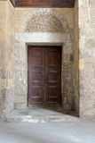Wooden aged ornate door and stone wall Royalty Free Stock Photo